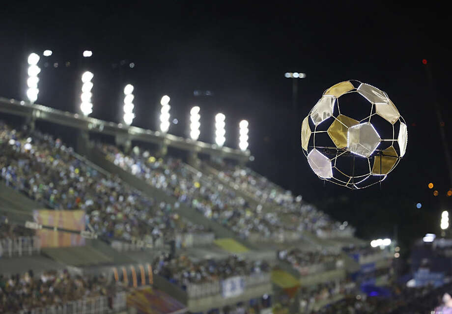 A drone, carrying a lightweight designed soccer ball, flies over the Portela samba school performers, in the Carnival parade at the Sambadrome in Rio de Janeiro, Brazil, Tuesday, Feb. 17, 2015. (AP Photo/Leo Correa)
