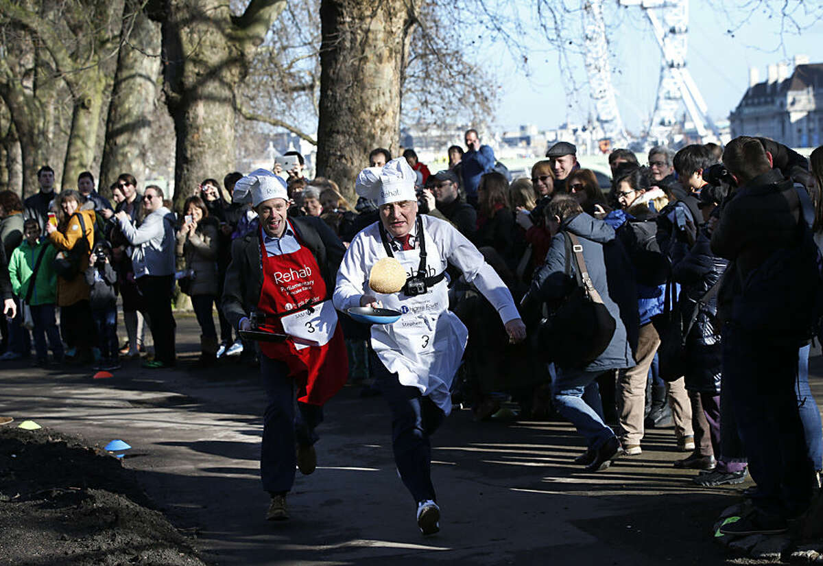Media team competitor Sam Macrory, left, competes with MP Stephen Pound, right, as they race during the 2015 Parliamentary Pancake Race, Tuesday, Feb. 17, 2015. The race saw Lords, MPs and members of the parliamentary press corps racing to raise awareness of the need to support disable people, according to the organizers. (AP Photo/Lefteris Pitarakis)