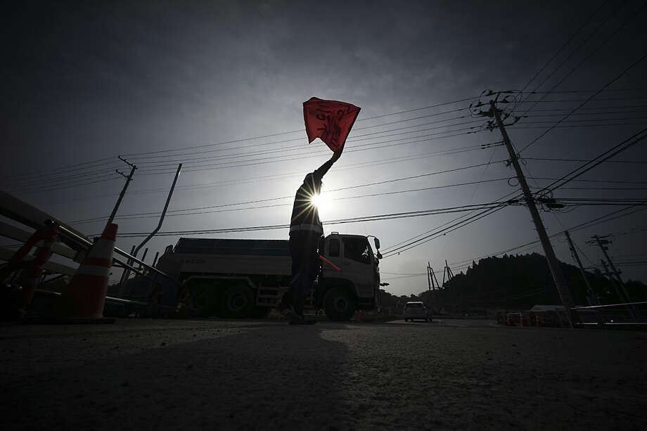 In this Tuesday, March 8, 2016 photo, a truck guide controls the traffic at the entrance of a reconstruction area in Minamisanriku, Miyagi Prefecture, northern Japan. Japan on Friday, March 11 marked the fifth anniversary of the powerful earthquake and tsunami that hit Japan, swallowing coastal villages, leaving more than 18,000 people dead or missing and devastating large swaths of the country's northeastern coastal area. Some places are still unlivable and require massive reconstruction to restore infrastructure, houses and people's lives. (AP Photo/Eugene Hoshiko)