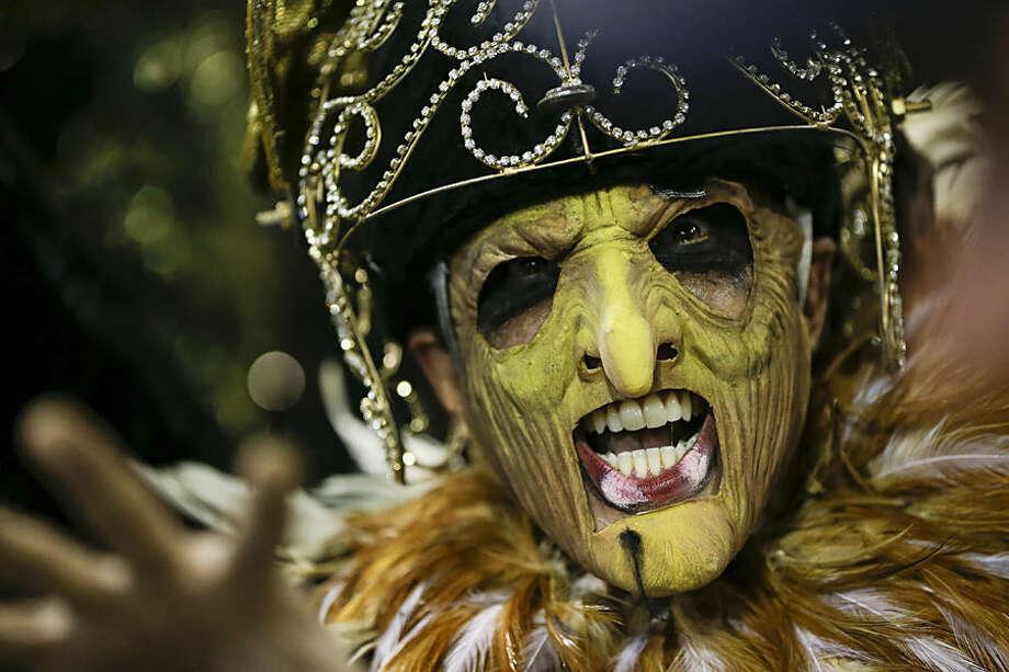 A performer from the Sao Clemente samba school, strikes a pose during the Carnival parade at the Sambadrome in Rio de Janeiro, Brazil, Monday, Feb. 16, 2015. (AP Photo/Felipe Dana)