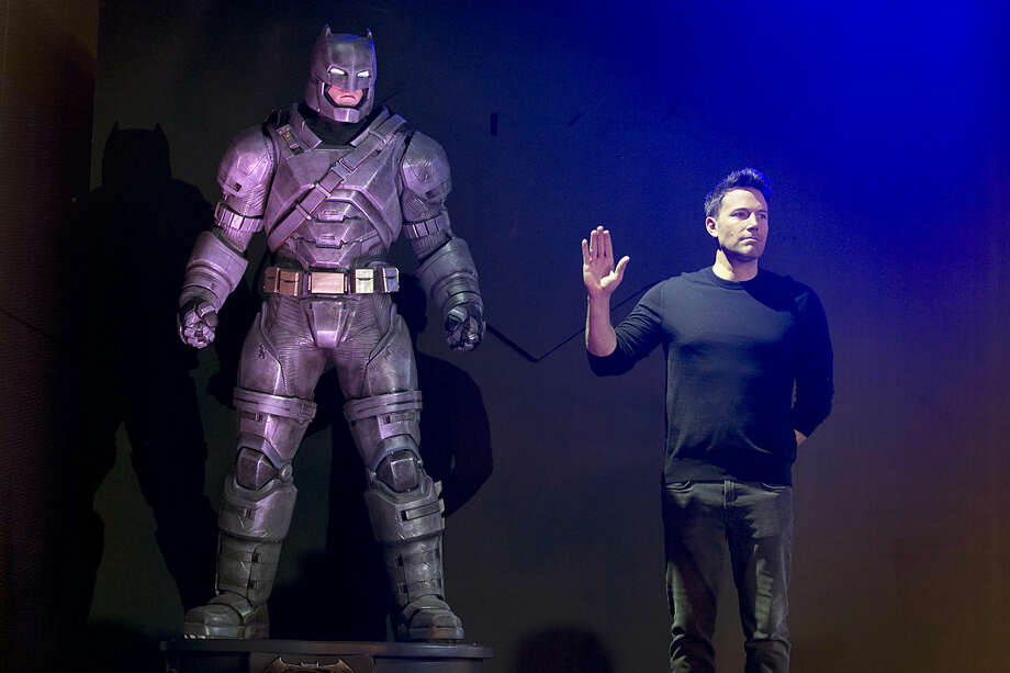 """Actor Ben Affleck poses with a statue of Batman during a press conference for the movie """"Batman v Superman: Dawn of Justice"""" in Beijing, China, Friday, March 11, 2016. (AP Photo/Ng Han Guan)"""