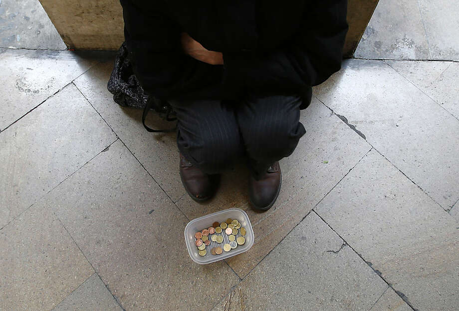 A woman begs for money in Milan, Italy, Friday, March 11, 2016. European Central Bank launched an unexpectedly broad array of stimulus measures Thursday aimed at boosting a modest economic recovery in the 19 countries that use the euro and nudging up dangerously low inflation. (AP Photo/Antonio Calanni)
