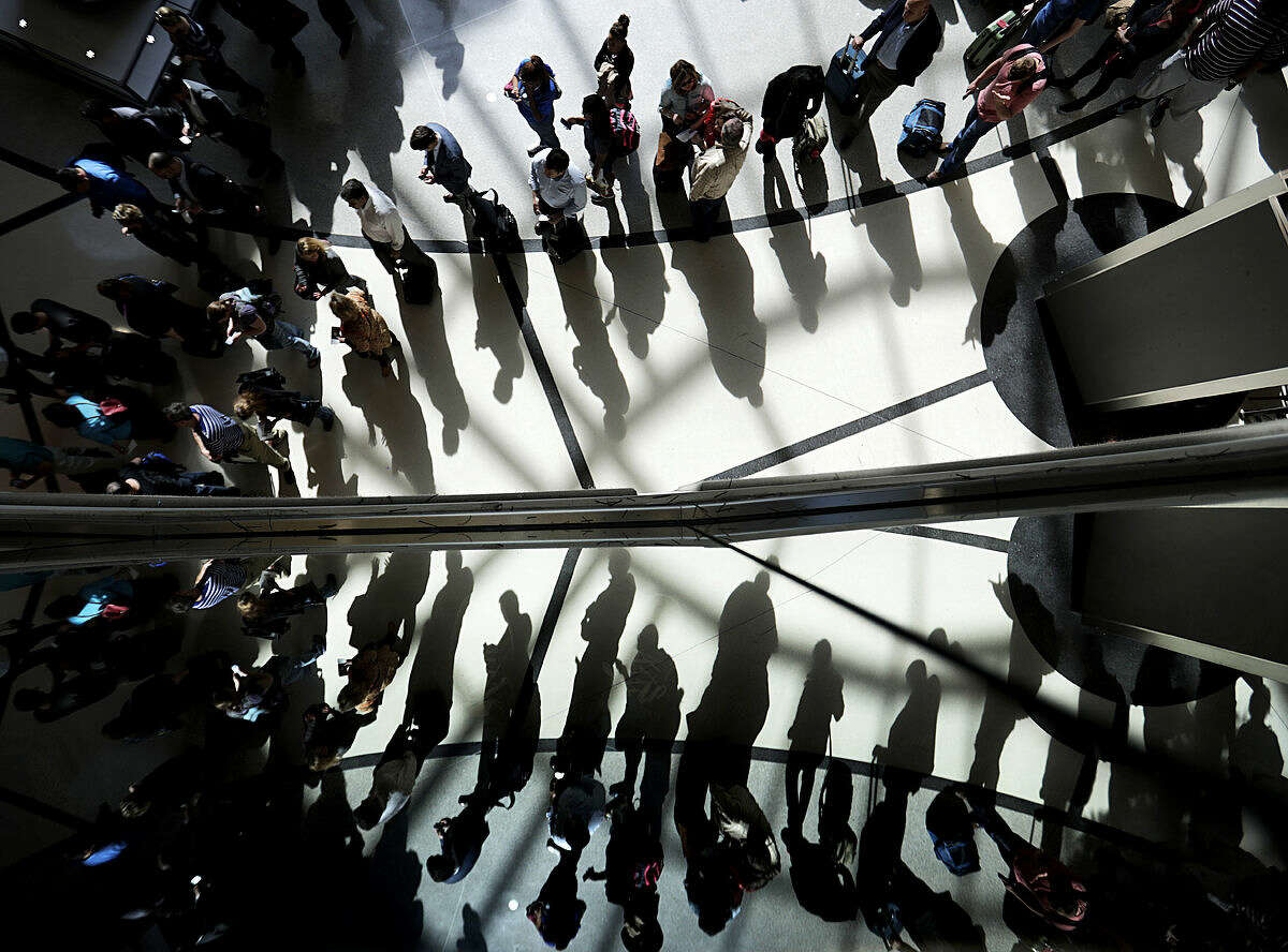 Passengers are reflected in glass as they line up to go through a security checkpoint under the atrium of the domestic passenger terminal at Hartsfield-Jackson Atlanta International Airport on Thursday, March 10, 2016, in Atlanta. Updates to the interior of the domestic passenger terminal and concourses, new parking decks, a sixth runway, and a 400-room hotel are part of a $6 billion expansion and renovation project at the world's busiest airport during the next 20 years, officials announced Thursday. (AP Photo/David Goldman)