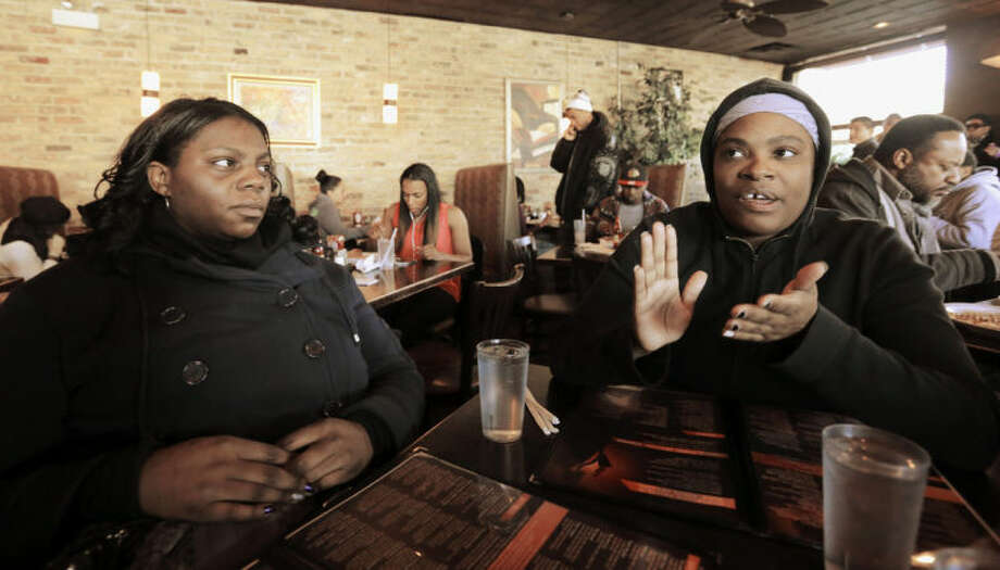 This Friday, Feb. 7, 2014 photo shows Christina English, right, a resident of Chicago's Bronzeville neighborhood resident, sitting with her friend Jeri Bryant from Cleveland, at a popular lunch spot speaking the possibility of a Barack Obama presidential library in the neighborhood. Bronzeville, the city's historic center of black culture, business and politics, is one of six potential Chicago sites bidding to be the location for a presidential library, each backed by different interests. English, who works with special-needs children, said an Obama library would be great for the area. (AP Photo/M. Spencer Green)