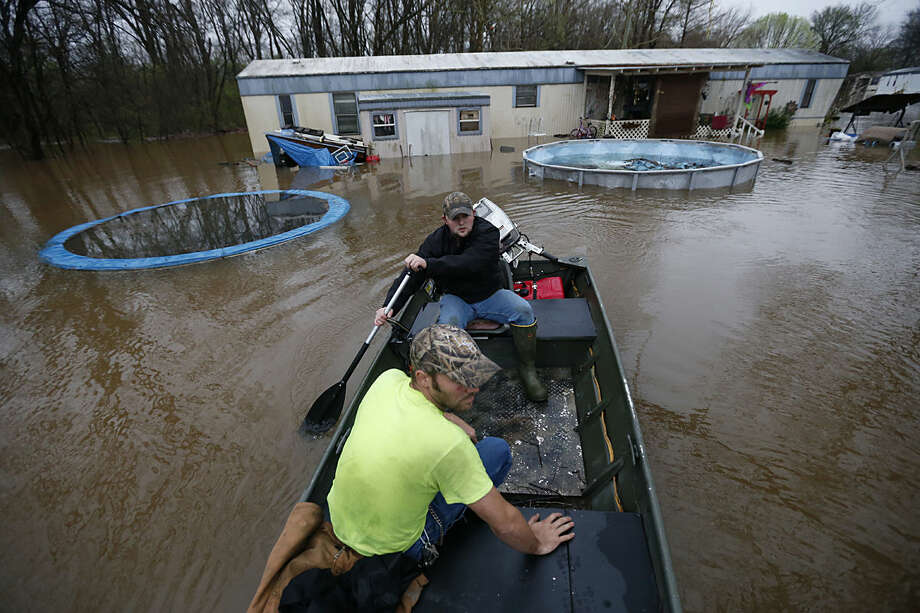 Sam Breen paddles his skiff as he helps his friend Roger Dove, foreground, retrieve his pets and some belongings from his home in rising water at the Pecan Valley Estates trailer park in Bossier City, La., Wednesday, March 9, 2016. (AP Photo/Gerald Herbert)