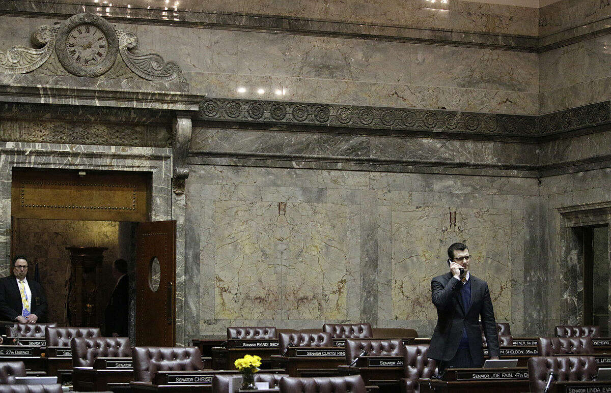 Rep. Joe Fain, R-Auburn, talks on a phone in the nearly empty Senate chamber, Thursday, March 10, 2016, at the Capitol in Olympia, Wash., shortly before