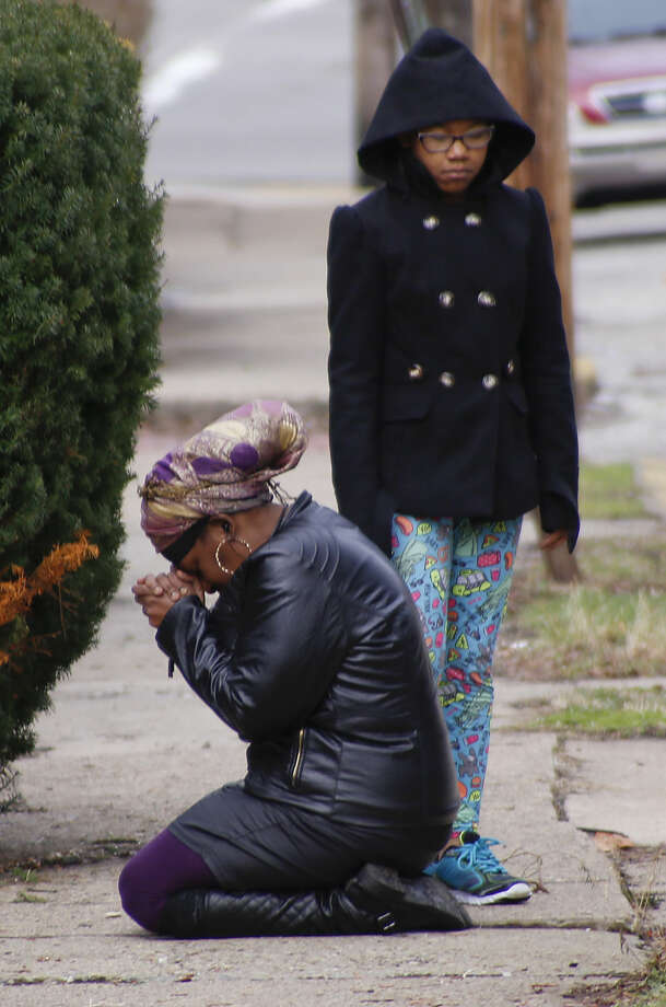 Carla Brown, left, prays as her daughter stands by in front of a house, Friday, March 11, 2016, where a shooting at a backyard party killed and wounded multiple people in Wilkinsburg, Pa. on Wednesday night. Brown said she was a close friend of the family that was attacked. (AP Photo/Keith Srakocic)