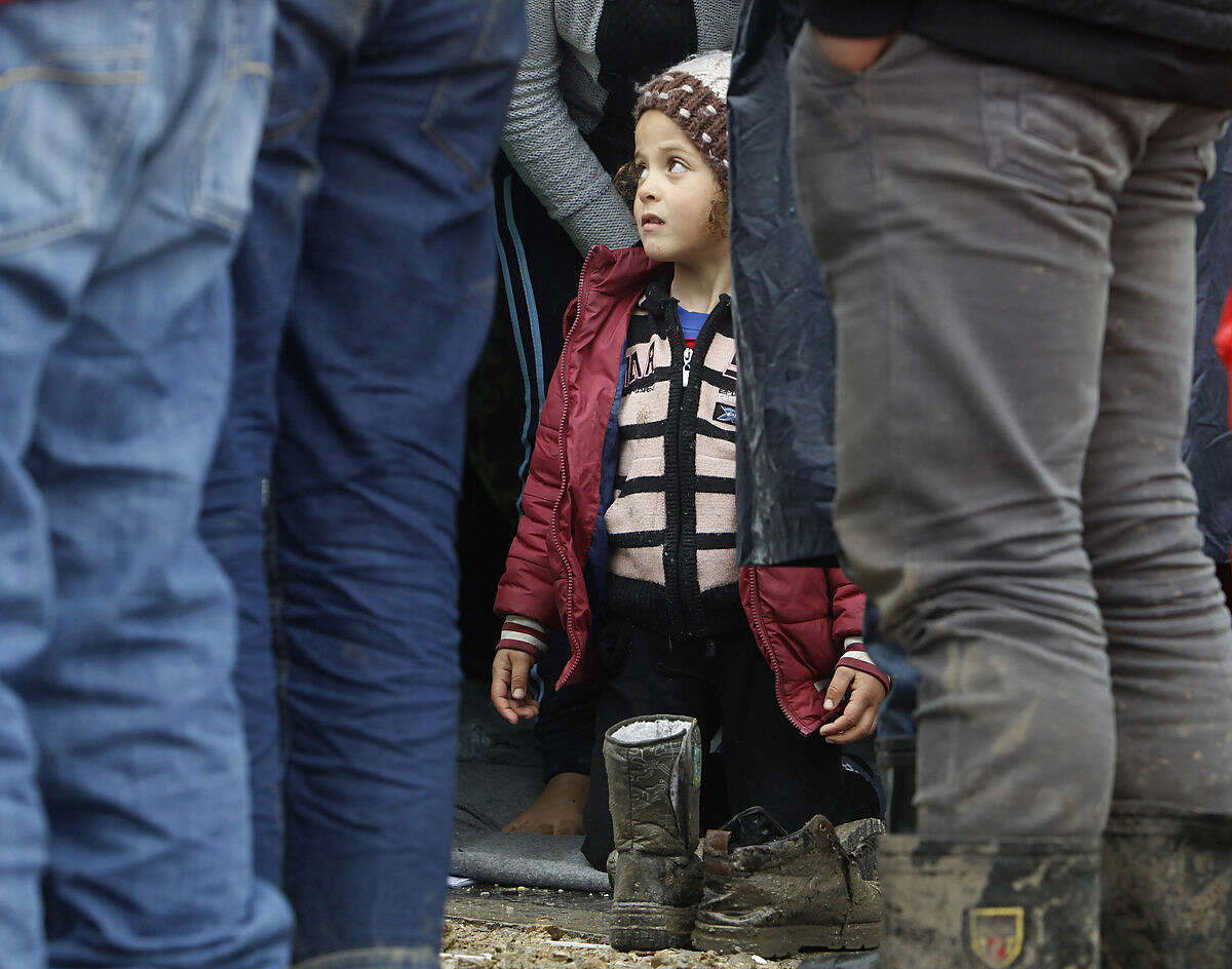 A Syrian refugee girl kneels on a tent, as men stand in front, in an improvised camp on the border line between Macedonia and Serbia near the northern Macedonian village of Tabanovce, Friday, March 11, 2016. About 1,500 refugees remain stranded at the Macedonian border with Serbia as the borders on the Balkan migrant route are closing. (AP Photo/Boris Grdanoski)