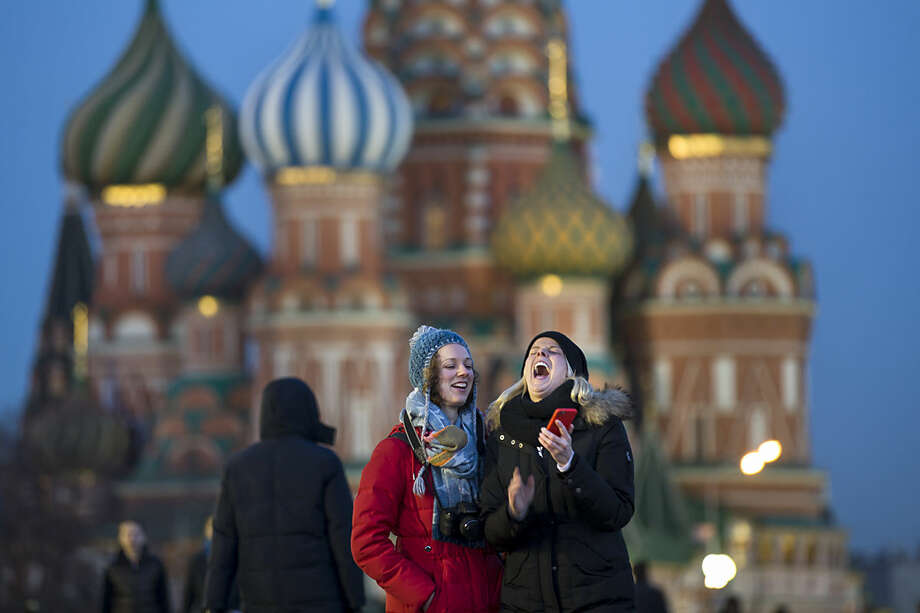 Tourists take a selfie in front of St. Basil Cathedral in Red Square in Moscow, Russia, Thursday, March 10, 2016. (AP Photo/Alexander Zemlianichenko)