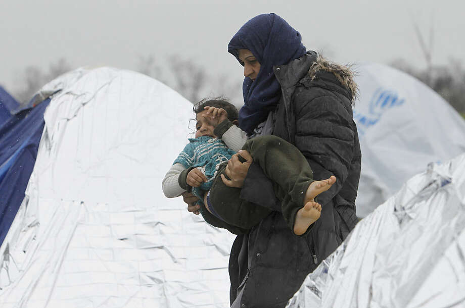 A Syrian refugee woman with a child walks in the rain among tents in an improvised camp on the border line between Macedonia and Serbia near the northern Macedonian village of Tabanovce, Thursday, March 10, 2016. Around 1.500 migrants and refugees are stranded at Tabanovce transit center for refugees in northern Macedonia. (AP Photo/Boris Grdanoski)
