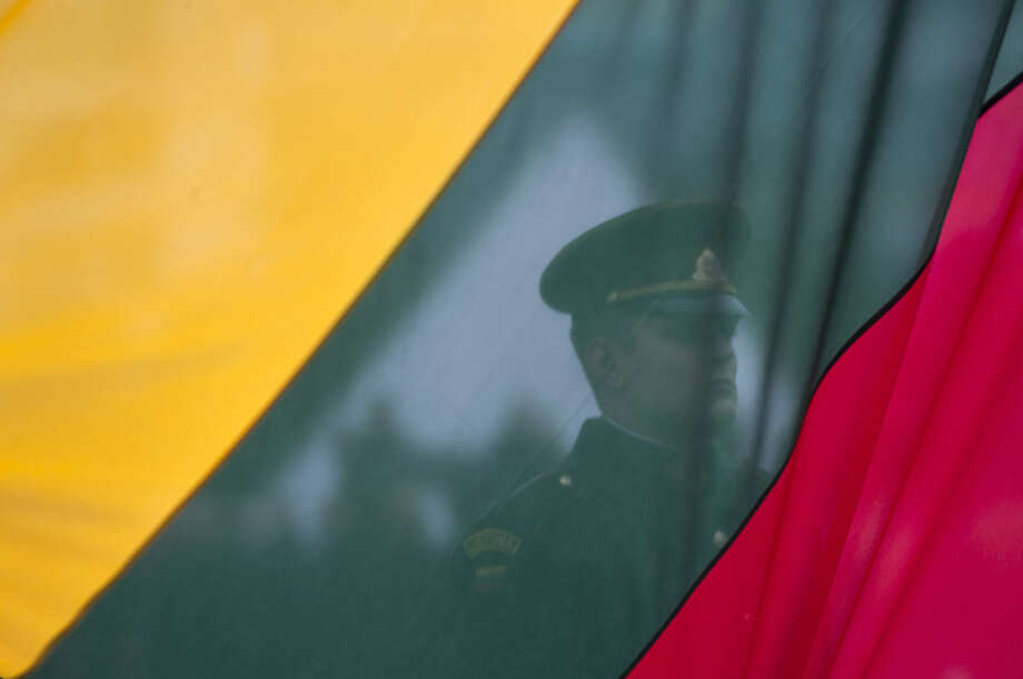 A Lithuanian soldier is seen behind a national flag being raised, during a celebration of Lithuania's independence in Vilnius, Lithuania, Friday, March 11, 2016. Lithuania celebrated the 26 anniversary of its declaration of independence from the Soviet Union on Friday, recalling the seminal events that set the Baltic nation on a path to freedom and helped lead to the collapse of the U.S.S.R. (AP Photo/Mindaugas Kulbis)