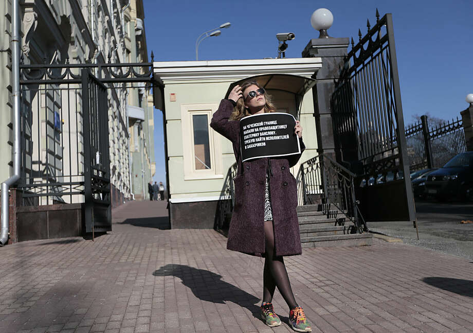A human rights activist holds a poster as she pickets Russian President's Administration building in Moscow, Russia on Thursday, March 10. 2016. The Committee to Protect Journalists is blaming Russian authorities' inattention to anti-media hostility as enabling the attack near Chechnya that left six journalists injured. The CPJ's statement Thursday came a day after attackers intercepted a small bus carrying activists and journalists, beat them and set the vehicle afire. The poster reads: Human rights activist Yekaterina Vanslova was attacked at Chechen border, I demand that attackers and organizers should be found. (AP Photo/Ivan Sekretarev)