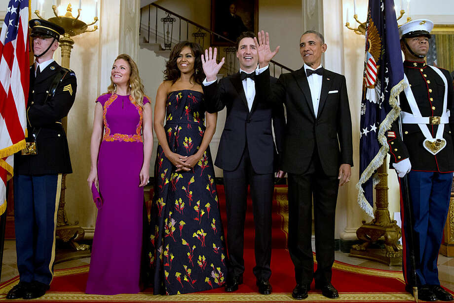 President Barack Obama, right, and Canadian Prime Minister Justin Trudeau, both wave next to Sophie Grégoire Trudeau, left, and first lady Michelle Obama, during a photograph at the White House during the State Dinner in Washington, Thursday, March 10, 2016. (AP Photo/Jacquelyn Martin)