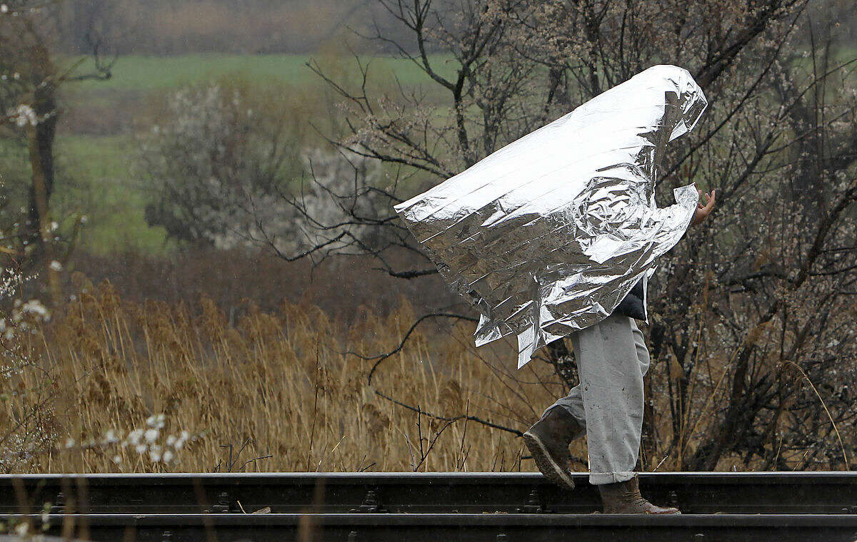 A man covered with thermal blanket walks along railway tracks beside an improvised refugee camp on the border line between Macedonia and Serbia near the northern Macedonian village of Tabanovce, Thursday, March 10, 2016. Around 1.500 migrants and refugees are stranded at Tabanovce transit center for refugees in northern Macedonia. (AP Photo/Boris Grdanoski)