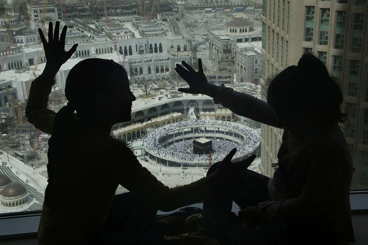 Children play at the glass windows of a hotel overlooking the Grand Mosque, in the Muslim holy city of Mecca, Saudi Arabia, Friday, March 11, 2016. (AP Photo/Amr Nabil)