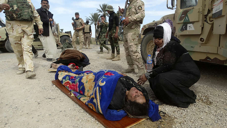 In this Wednesday, March 9, 2016 photo, an injured woman comforts another as they wait for treatment after clashes between Iraqi Security forces and Islamic State group extremists in a village outside Ramadi, 70 miles (115 kilometers) west of Baghdad. Iraqi forces are trying to build on their recent gains in Ramadi to clear Islamic State group fighters from areas leading to the IS-held city of Mosul to the north. (AP Photo/Osama Sami)