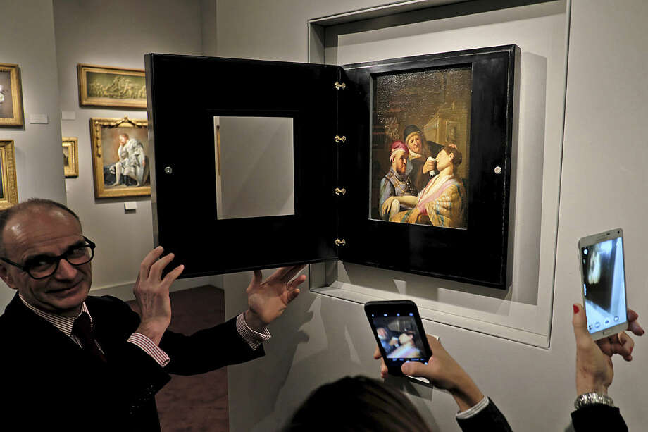 Gallery owner Bertrand Gautier, left, shows visitors to the booth of Galerie Talabardon & Gautier at the TEFAF fine art fair the newly discovered painting by Dutch master Rembrandt titled The Unconscious Patient (Sense of Smell) dated at around 1624-25, oil on panel 21.6x17.8 cm, in Maastricht, southern Netherlands, Thursday, March 10, 2016. (AP Photo/Mike Corder)