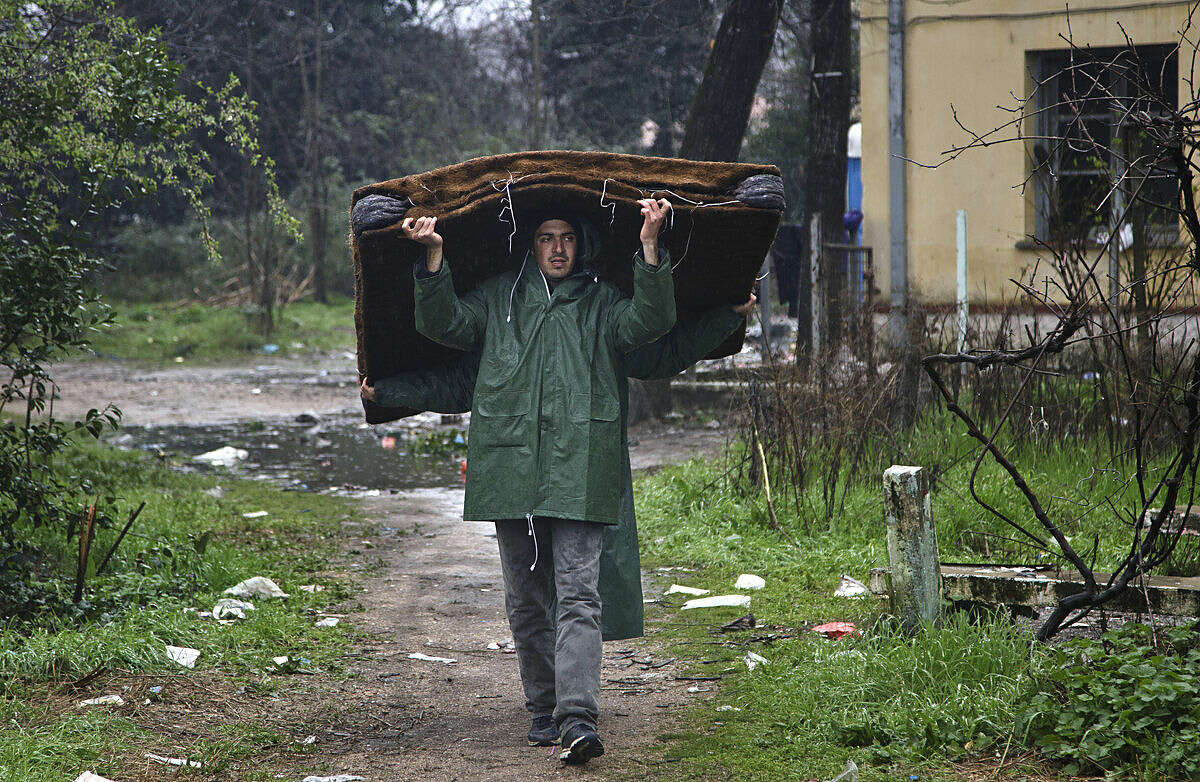 Migrants carry a mattress at the Greek border camp near Idomeni, Thursday, March 10, 2016. Northbound borders are closed and authorities plan to distribute fliers telling refugees seeking to reach central Europe that there is no hope of you continuing north, therefore come to the camps where we can provide assistance as more than 36,000 transient migrants are thought to be stuck in financially struggling Greece. (AP Photo/Visar Kryeziu)