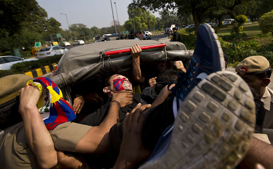 Tibetan exiles shouting anti China slogans outside the Chinese embassy are put in a police car as they protest to mark the 57th anniversary of the March 10, 1959, Tibetan Uprising Day, in New Delhi, India, Thursday, March 10, 2016. (AP Photo/Saurabh Das)