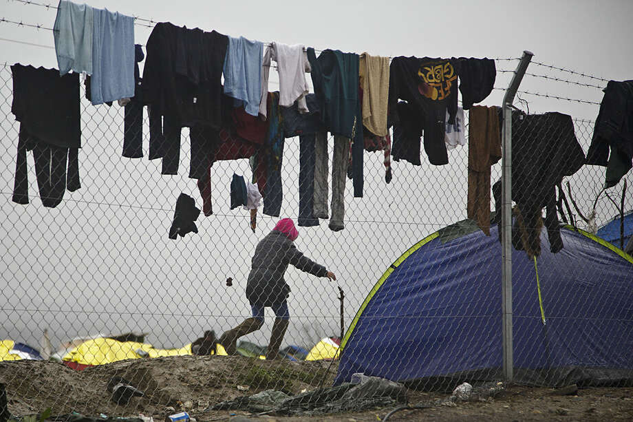 Migrant runs among clothes hanged to dry on a fence at the Greek border camp near Idomeni, Thursday, March 10, 2016. After nearly three days of rain, conditions in the refugee camp on the Greek-Macedonian where about 14,000 people are stranded have deteriorated significantly, with many of its residents struggling to re-pitch their small camping tents in slightly drier patches. (AP Photo/Visar Kryeziu)