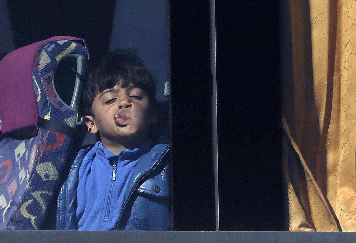 A migrant boy presses his face against the window of a bus at the Athens' port of Piraeus on Thursday, March 10, 2016. Authorities began transporting hundreds of migrants and refugees from Piraeus port to shelters in central Greece to try and ease overcrowding there. The government says nearly 42,000 people are stranded in Greece following border restrictions and closures by Austria and several Balkan countries that started last month. (AP Photo/Thanassis Stavrakis)