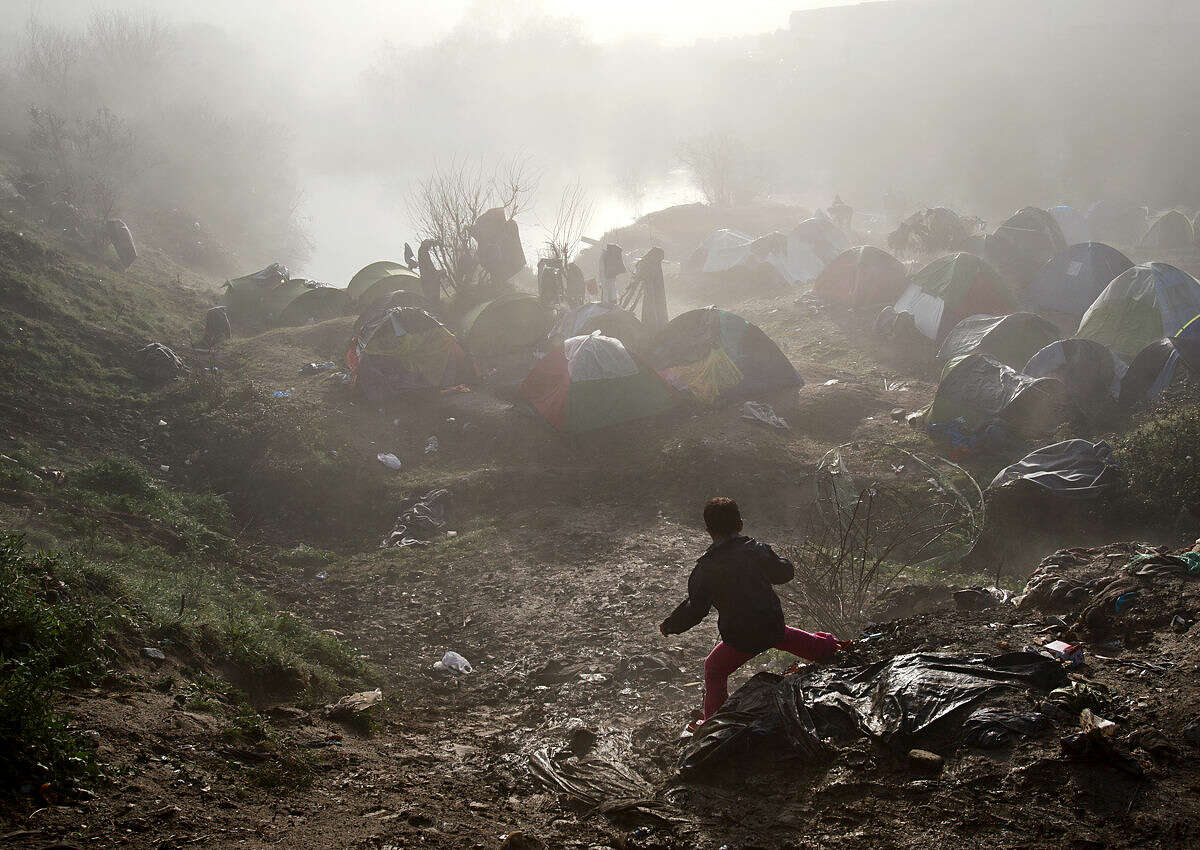 A boy walks down a muddy slope on a foggy morning at the northern Greek border station of Idomeni, Friday, March 11, 2016. After nearly three days of rain, conditions in the refugee camp on the Greek-Macedonian where about 14,000 people are stranded have deteriorated significantly, with many of its residents struggling to re-pitch their small camping tents in slightly drier patches.(AP Photo/Vadim Ghirda)