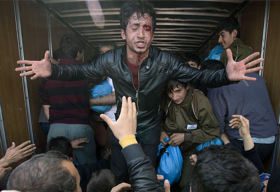 An injured man pleads with crowds of migrants scuffling to grab aid from a truck at the northern Greek border station of Idomeni, Friday, March 11, 2016. After nearly three days of rain, conditions in the refugee camp on the Greek-Macedonian where about 14,000 people are stranded have deteriorated significantly, with many of its residents struggling to re-pitch their small camping tents in slightly drier patches.(AP Photo/Vadim Ghirda)