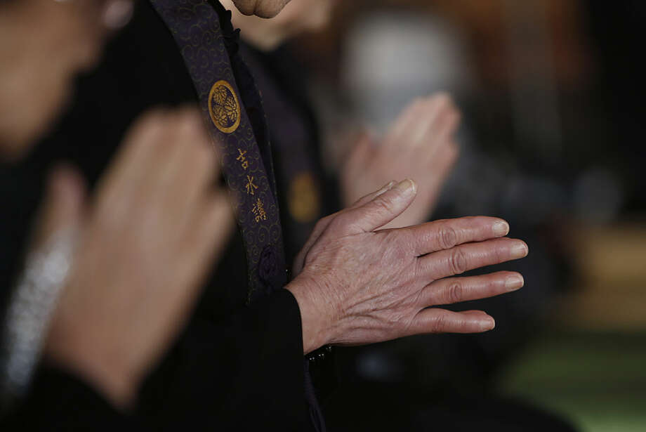 People clasp their hands as they pray for the victims of the March 11, 2011 earthquake and tsunami at Jyodoji Temple in Rikuzentakata, Iwate Prefecture, northeastern Japan, Friday, March 11, 2016. Japanese gathered in Tokyo and along the country's ravaged northeast coast to observe a moment of silence at 2:46 p.m. Friday, exactly five years after a magnitude 9.0-earthquake struck offshore and triggered a devastating tsunami that killed more than 18,000 people. (AP Photo/Koji Ueda)