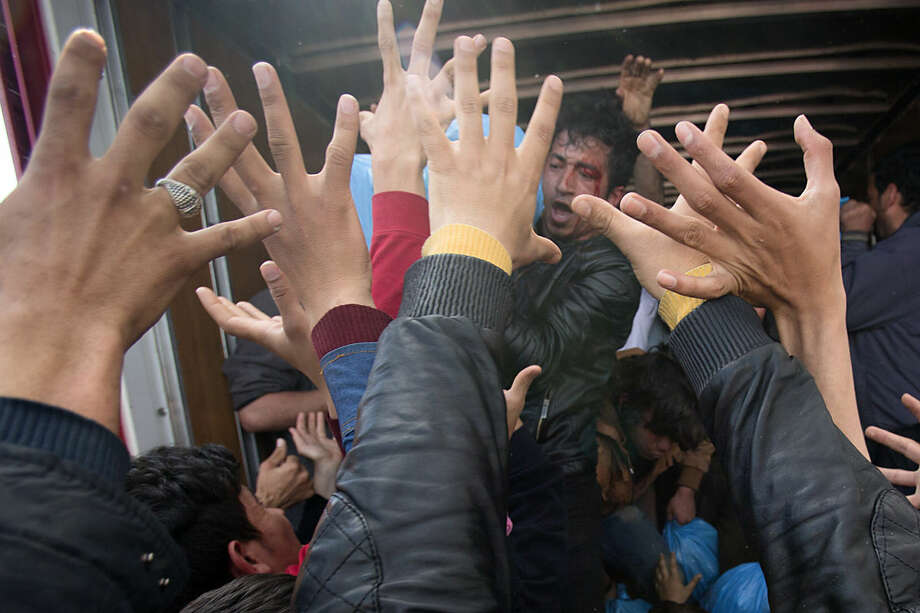 An injured man throws aid from a truck to a crowd of migrants at the northern Greek border station of Idomeni, Friday, March 11, 2016. After nearly three days of rain, conditions in the refugee camp on the Greek-Macedonian where about 14,000 people are stranded have deteriorated significantly, with many of its residents struggling to re-pitch their small camping tents in slightly drier patches.(AP Photo/Vadim Ghirda)