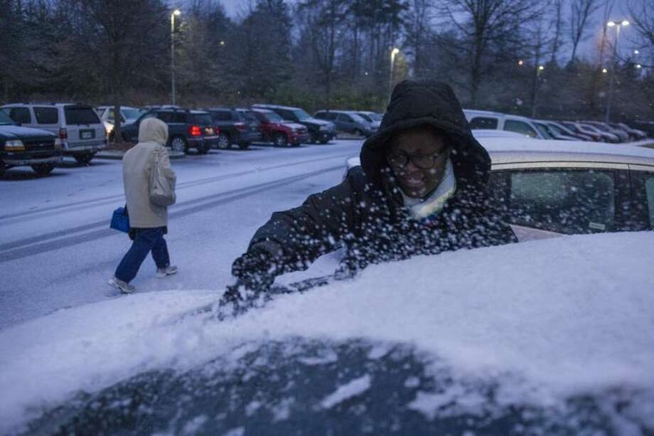 Shmetrice Moore, a nurse at an Emory hospital, scrapes snow and ice off her windshield as she and others are released early from their shift before a winter storm on Wednesday, Feb. 12, 2014, in Johns Creek, Ga. From Texas to the Carolinas and the South's business hub in Atlanta, roads were slick with ice, tens of thousands were without power, and a wintry mix fell in many areas. (AP Photo/John Amis)