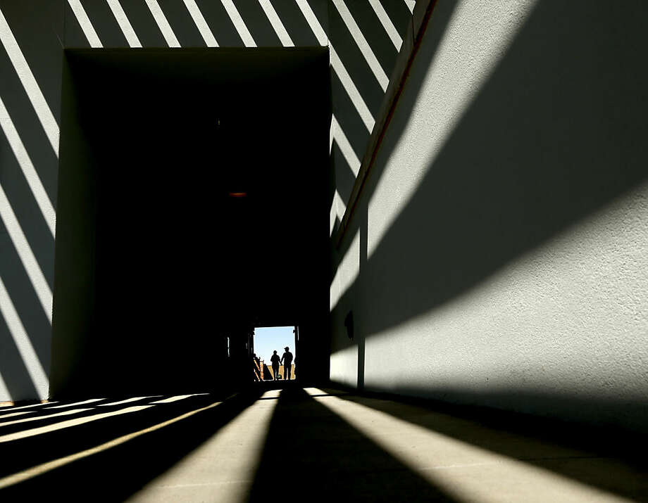People walk through a concourse at Peoria Sports Complex before a spring training baseball game between the Seattle Mariners and the Chicago Cubs Thursday, March 10, 2016, in Peoria, Ariz. (AP Photo/Charlie Riedel)