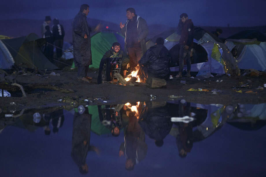Migrants gather around a fire at the Greek border camp near Idomeni, Thursday, March 10, 2016. After nearly three days of rain, conditions in the refugee camp on the Greek-Macedonian where about 14,000 people are stranded have deteriorated significantly, with many of its residents struggling to re-pitch their small camping tents in slightly drier patches. (AP Photo/Visar Kryeziu)