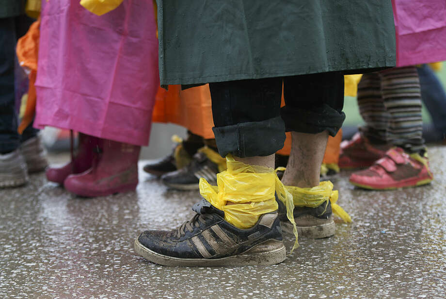 A man wears plastic sheets wrapped around his feet as mud protection while waiting for food handouts during a rainfall at the northern Greek border station of Idomeni, Thursday, March 10, 2016. After nearly three days of rain, conditions in the refugee camp on the Greek-Macedonian where about 14,000 people are stranded have deteriorated significantly, with many of its residents struggling to re-pitch their small camping tents in slightly drier patches. (AP Photo/Vadim Ghirda)