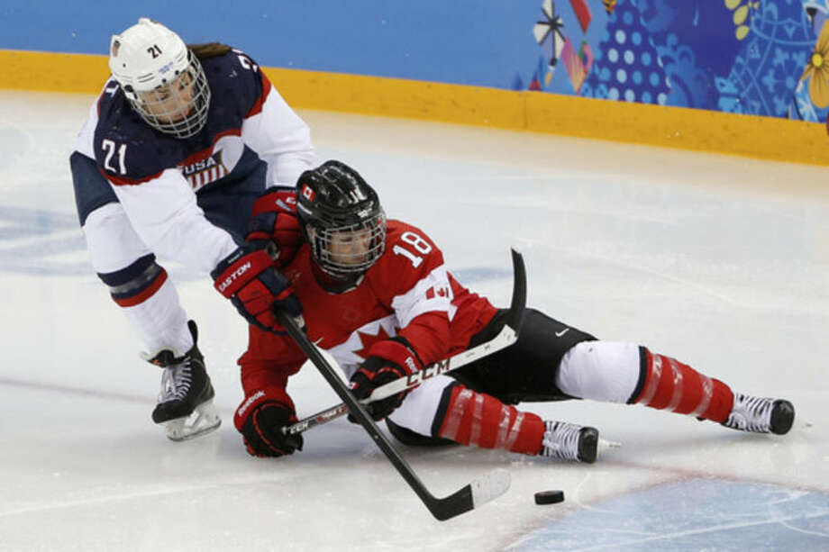 Hilary Knight of the United States and Catherine Ward of Canada battle for control of the puck during the 2014 second period of the Winter Olympics women's ice hockey game at Shayba Arena, Wednesday, Feb. 12, 2014, in Sochi, Russia. (AP Photo/Petr David Josek)