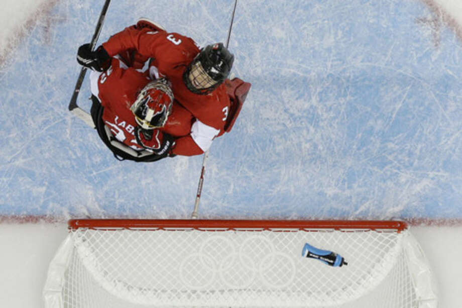 Jocelyne Larocque (3) hugs goalkeeper Charline Labonte of Canada after their 3-2 victory over the United States during the 2014 Winter Olympics women's ice hockey tournamanet at Shayba Arena, Wednesday, Feb. 12, 2014, in Sochi, Russia. (AP Photo/Matt Slocum)