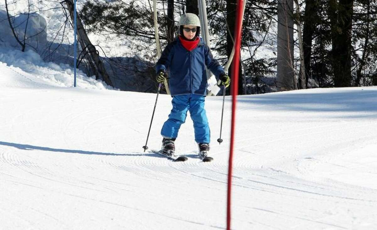 In this photo Thursday Jan. 30, 2014 taken 8-year-old Elliot Phifer navigates turns through the terrain-based learning center at Cranmore Mountain ski area in North Conway, N.H. The terrain-based learning center is a new way to teach new skiers how to ski and not be afraid of the mountain.(AP Photo/Jim Cole)