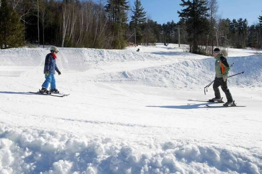 In this photo taken Thursday Jan. 30, 2014 ski instructor Dave Bartlett watches new skier 8-year-old Elliot Phifer navigate through the traverse trax section at the terrain-based learning center at Cranmore Mountain ski area in North Conway, N.H. The terrain-based learning center is a new way to teach new skiers how to ski and not be afraid of the mountain. (AP Photo/Jim Cole)