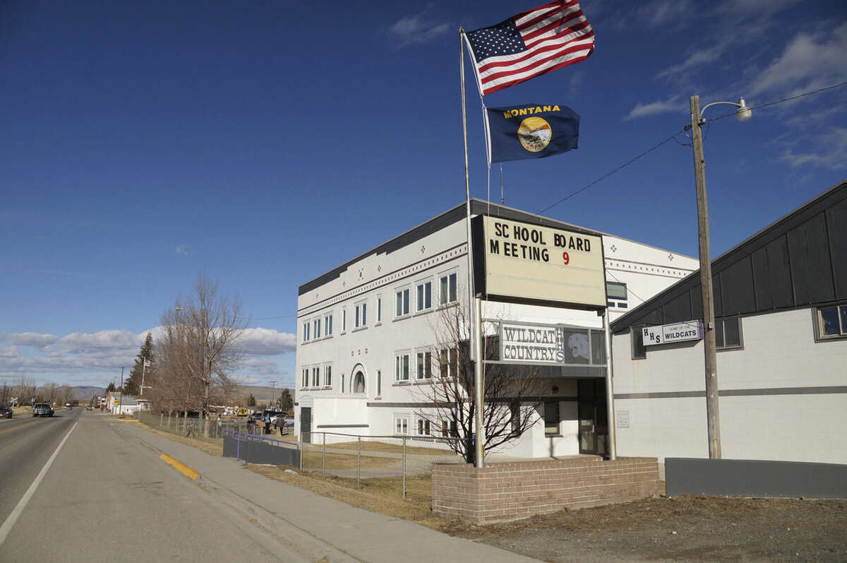 In this Jan. 28, 2015 photo, an American flag and a Montana state flag fly in front of Harrison High School, in Harrison, Mont. Harrison High School in 2013 banned a student after he brought two handguns to school. Now, after that student has served a year in a juvenile facility and received two years of counseling, the child's parents are having a hard time finding a school in the state that will accept their child, now 16, and who they say has changed for the better. (AP Photo/Alison Noon)