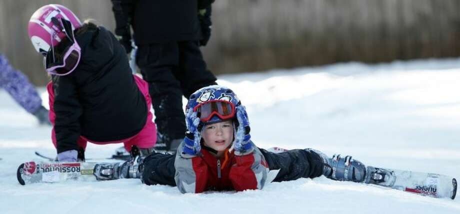 In this photo taken Thursday Jan. 30, 2014 a young skier is seen after falling in the terrain-based mini-pipe at Cranmore Mountain ski area in North Conway, N.H. The ski area is one of a few in the country that has started using terrain-based lessons to teach new skiers how to ski. (AP Photo/Jim Cole)