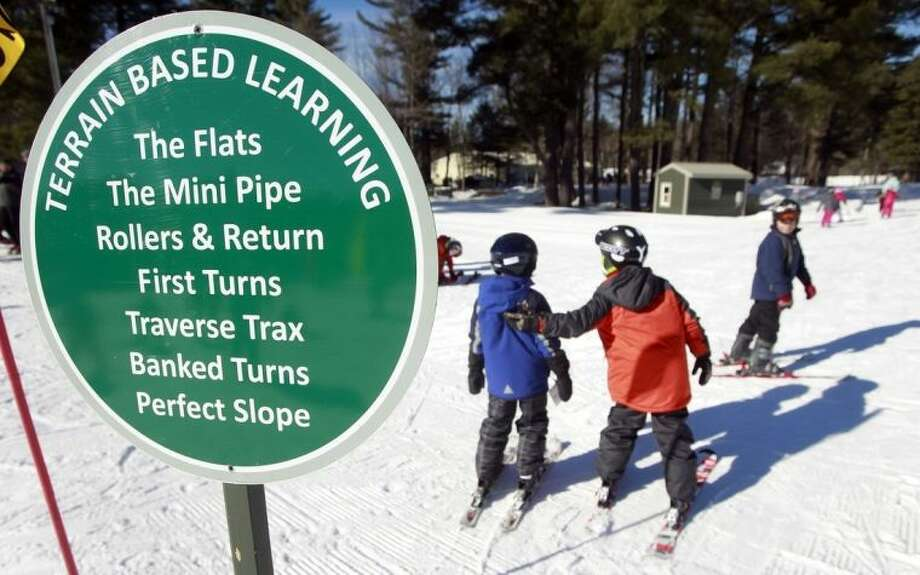 In this photo taken Thursday Jan. 30, 2014 beginner skiers make their way to the terrain-based learning center for new skiers at Cranmore Mountain ski area in North Conway, N.H. Instead of teaching new skiers how to stop first, terrain-based skiing teaches new skiers skills with banks, berms, and bumps that naturally slow them down without sliding down the mountain out of control. (AP Photo/Jim Cole)