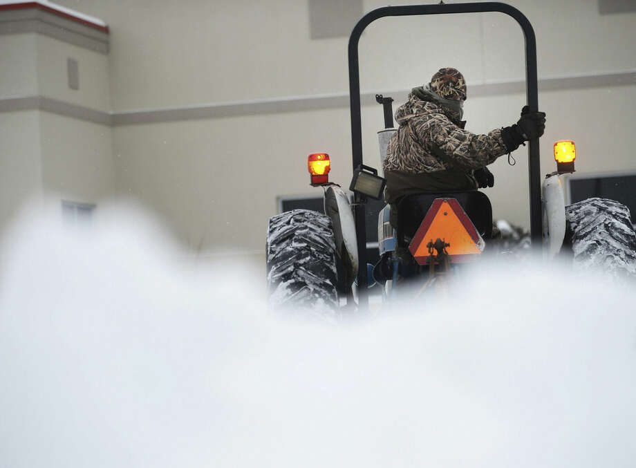 Duane Read clears snow at the Eastern Shore Family YMCA, Tuesday, Feb. 17, 2015, in Onley, Va. A snow and ice storm blasted parts of the Mid-Atlantic and the South on Tuesday, creating treacherous road conditions and leaving hundreds of thousands without power. (AP Photo/Jay Diem, Eastern Shore News) NO SALES