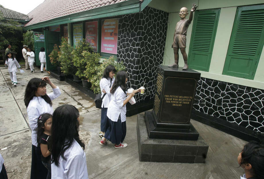 FILE - In this March 12, 2010, file photo, students walk near the statue of U.S. President Barack Obama as a boy at an elementary school he once attended in Jakarta, Indonesia. It was the darkest episode in Indonesia's modern history: a bloody anti-communist purge that left perhaps a half-million people dead. And it is one that is particularly poignant for Obama, who moved to Indonesia as a child right after the killings ended. Joko Widodo, the first directly elected Indonesian president without links to Suharto, ran as a reformer who would look into episodes of military impunity, but since taking office in 2014, he has not pressed the issue due to opposition within his own government and the still-powerful military. (AP Photo/Irwin Fedriansyah, File)