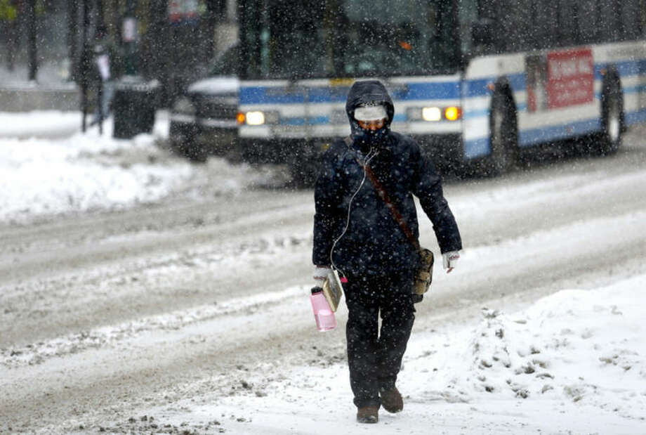 Sindy Buchanan of Portland trudges across Congress Street in the snow on her way home from work as a major storm hit Southern Maine Thursday, Feb. 13, 2014. (AP Photo/Portland Press Herald, Gabe Souza)