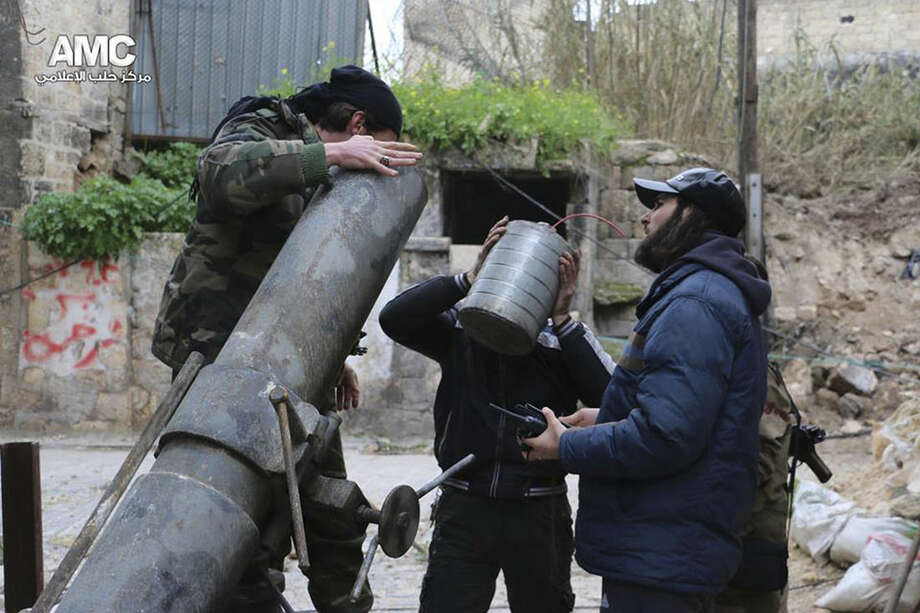 This photo provided on Sunday Feb. 15, 2015 by the Syrian anti-government activist group Aleppo Media Center (AMC), which has been authenticated based on its contents and other AP reporting, shows Syrian rebels preparing to fire locally made shells against the Syrian government forces, in Aleppo, Syria. Activists say Syrian rebels have regained much of an area north of the city of Aleppo that they lost to government troops in fierce fighting the previous day. The clashes have left more than 100 dead on both sides. (AP Photo/Aleppo Media Center, AMC)