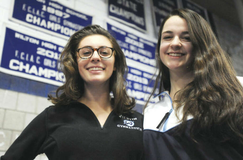 Hour photo/John NashWilton's Annie Saltarelli, left, and Meghan Graham, the co-captains of the Warriors gymnastics team, stand under the three previous banners the program has raised as three-time defending FCIAC champions. The Warriors are seeking their fourth straight title on Saturday.
