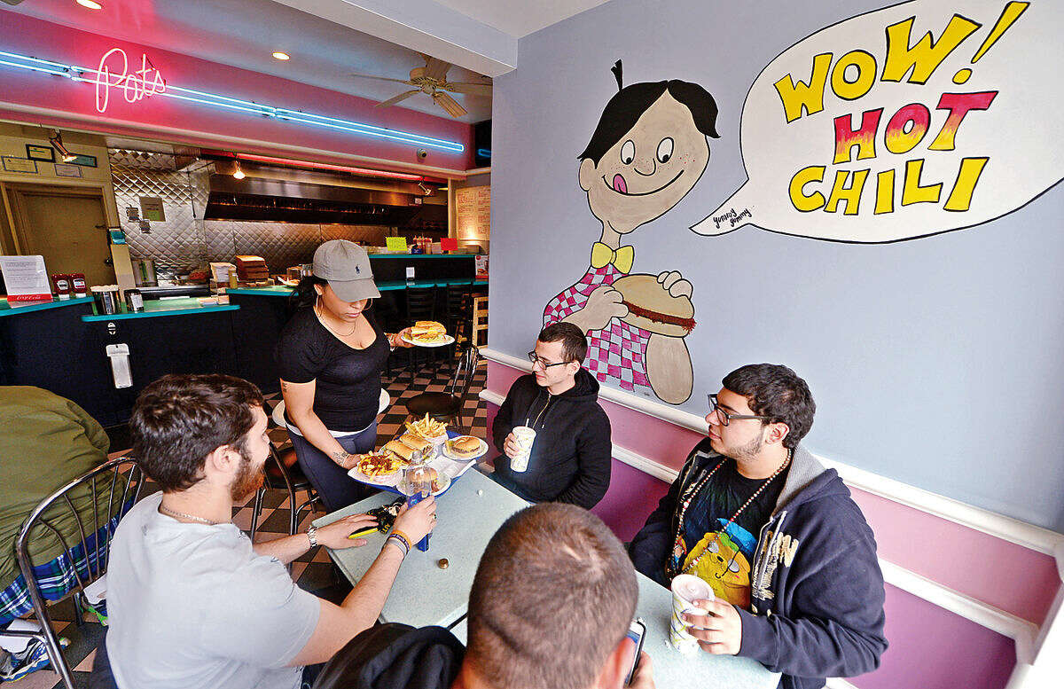 Hour photo / Erik Trautmann Employee Serina Dejesus serves patrons Dylan Malave, Anthony Orellano, Demitri Lodolce and Kervin Rivera at Pat's Hubba Hubba before it closes down Sunday after nearly 50 years of operation.