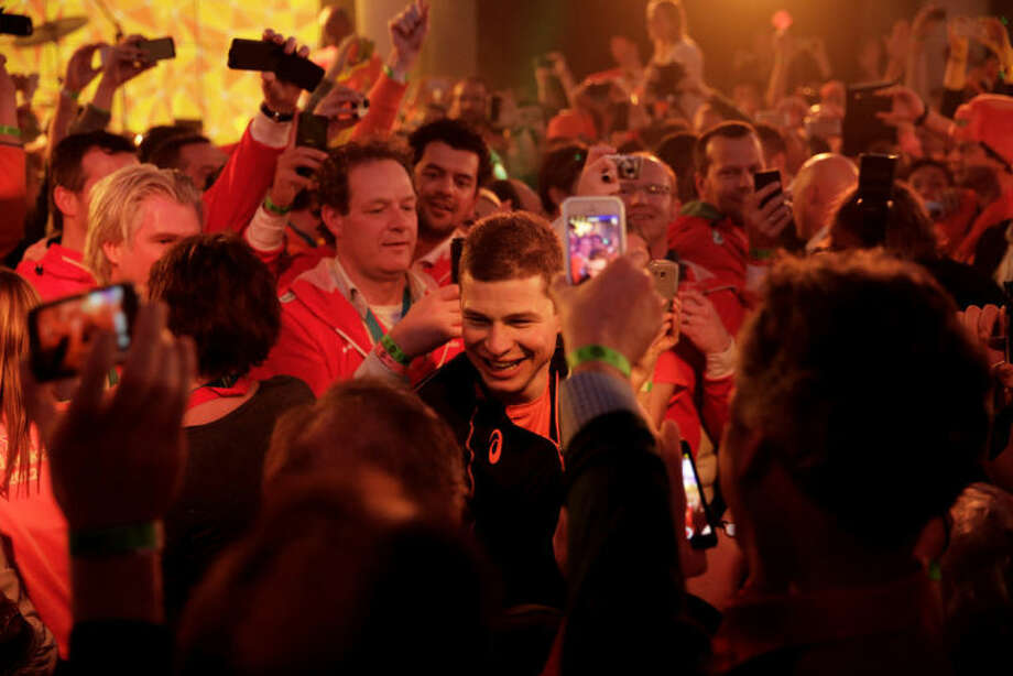 Under orange lighting, gold medallist Sven Kramer of the Netherlands walks through a crowd of cheering fans after winning the gold in the men's 5,000-meter speedskating race at the 2014 Winter Olympics in Sochi, Russia, Saturday, Feb. 8, 2014. Kramer set a new Olympic record in the race. (AP Photo/Matt Dunham)