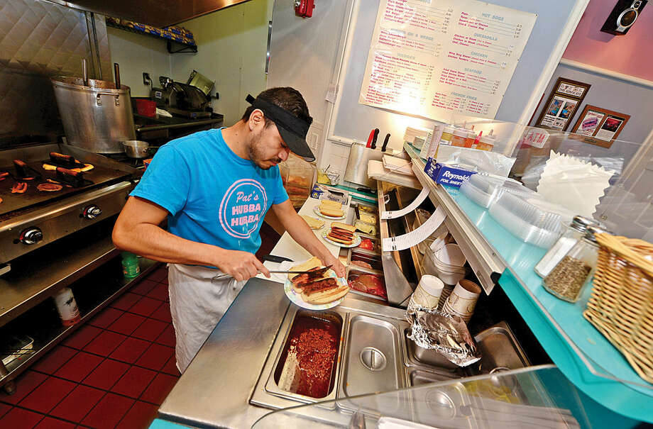 Hour photo / Erik Trautmann Juan Bravo makes chili dogs at Pat's Hubba Hubbawhich is closing it's doors Sunday after nearly 50 years of operation.