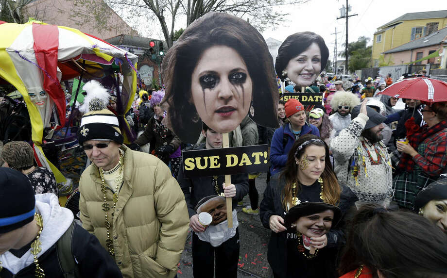 Revelers march with effigies of Rita Benson LeBlanc, granddaughter of New Orleans Saints owner Tom Benson, foreground, and his wife Gayle Benson, background, a reference to the current court battle over the team's future ownership, on Mardi Gras in New Orleans, Tuesday, Feb. 17, 2015. Revelers in glitzy costumes filled the streets of New Orleans for the annual fat Tuesday bash, opening a day of partying, parades and good-natured jostling for beads and trinkets tossed from passing floats. (AP Photo/Gerald Herbert)