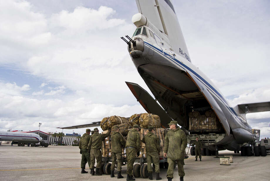 FILE - In this Wednesday, Jan. 20, 2016 file photo, Russian air force personnel prepare to load humanitarian cargo on board a Syrian Il-76 plane at Hemeimeem air base in Syria. Russia's defense ministry said Tuesday, March 15, 2016 that the first group of warplanes stationed at the Russian air base in Syria has left for home following a pullout order from President Vladimir Putin. (AP Photo/Vladimir Isachenkov, File)
